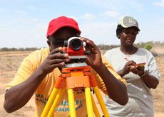 People working with surveying equipment in Africa