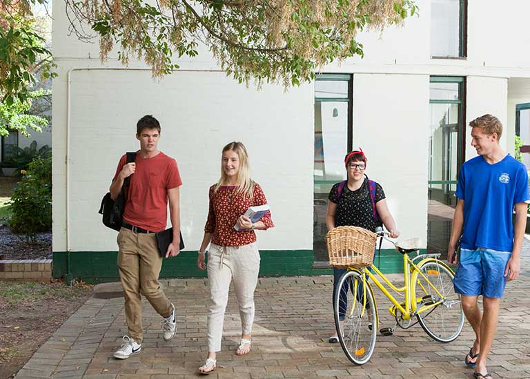 Four students walking together outside a college.