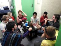 Group of students sitting around a tea caddy in the hallway of Earle Page College