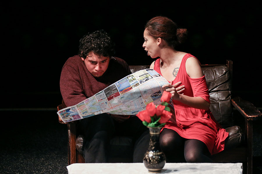 A young man and woman look surprised by a newspaper article in a stage production