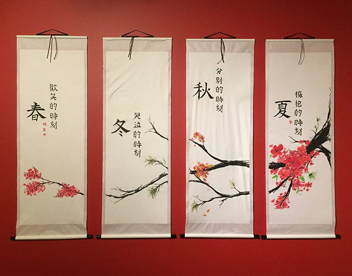 A watercolour cherry blossom branch crosses three silk-like hanging banners with Chinese characters
