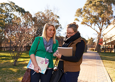 2 female students carrying books on Graduate's Walk with Dixson Library in the background
