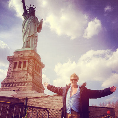 UNE student Max posing for a photoin front of the Statue of Liberty - New York
