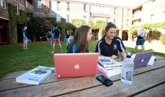 Two female students with books and laptops study at an outdoor table while other students play games in the background