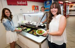 Three students serving themselves from the salad bar in Duval kitchen