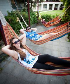 Students relaxing in a row of brightly coloured hammocks at Mary White college