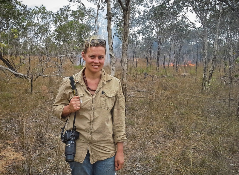 Michelle McKemey, with SLR camera over shoulder, standing in bush with fire in background