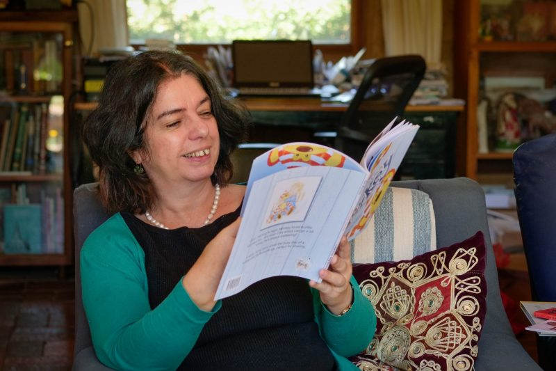 Sophie Mason in living room reading child's book