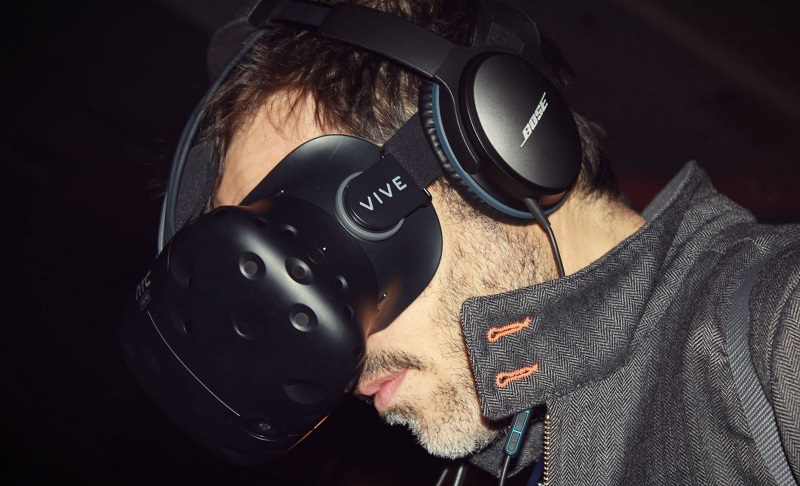 Young man wearing Vive virtual reality headset and Bose headphones