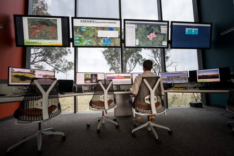 Man sitting at modern desk with banks of multiple computer screens displaying maps and data, in front of large windows revealing rural scene outside
