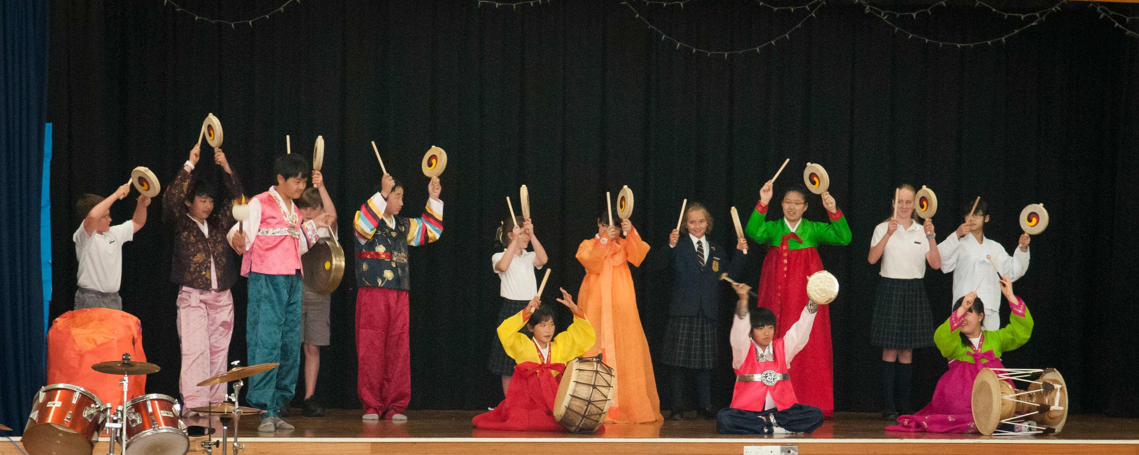 AKC Students playing musical instruments on stage