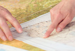 Hands pointing to a location on a map.