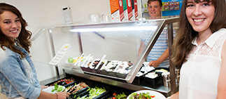 Three students serving themselves from the Duval kitchen salad bar.
