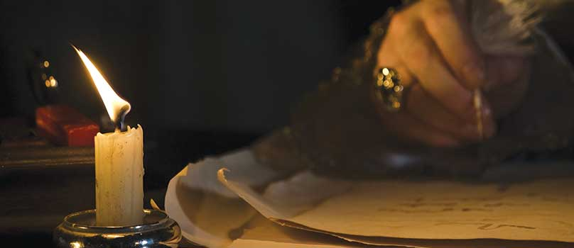 Atmospheric and historic image of a hand, a quill and a candle.
