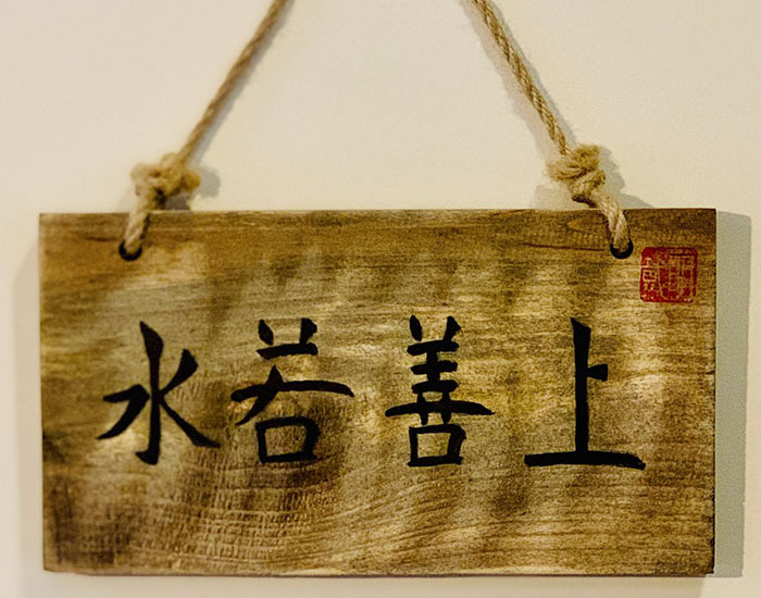 Artwork featuring a hanging wooden board with Chinese characters