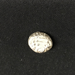 Small lump of metal that is an ancient coin