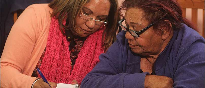 Lorina Barker and an indigenous woman writing down stories.