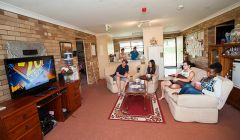 Students in living area of Wright Village unit, with lounges, coffee table and full kitchen