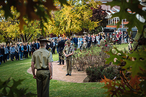 The 2017 Anazac Day Memorial Ceremony at UNE Memorial Rose Garden with two soldiers standing guard at the memorial watched by attendees.