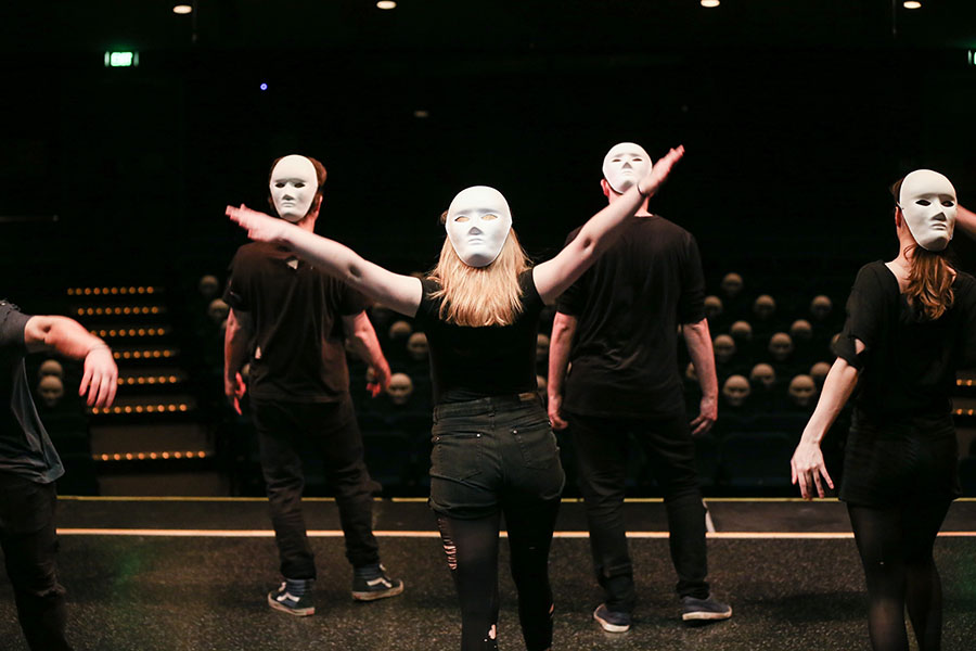 Three people on stage wear back-to-front plain white masks facing an audience of anonymous masked people