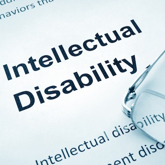 Intellectual disability printed on paper with reading glasses sitting on the paper.
