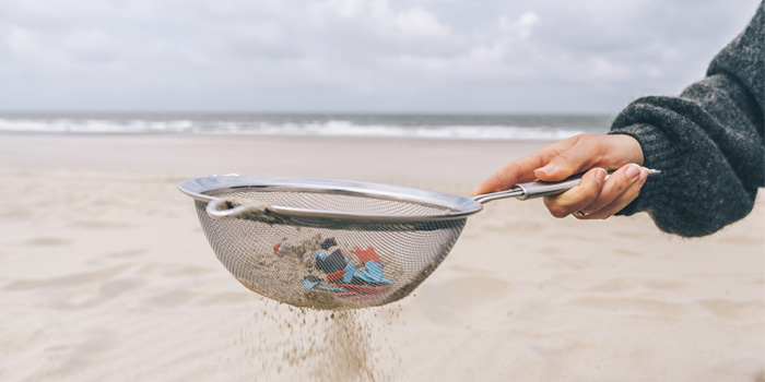 Sand and microplastics being filtered through a sieve on the beach