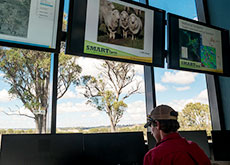 View from window of UNE SMART Farm Innovation Centre, showing bank of computer monitors inside and trees outside