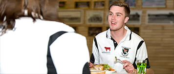 Male student eating chicken dinner and talking to another student out of frame