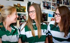 Three girls in Robb College shirts talking in front of a wall of photos