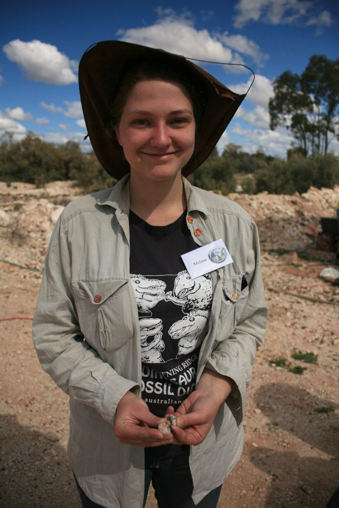 Previous dig participant and UNE student, Melissa Jones holding two dinosaur bones she discovered.