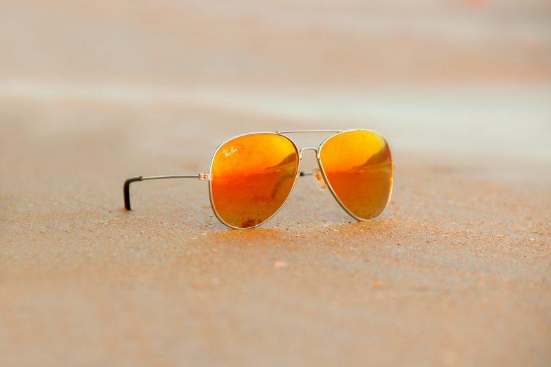 Pair of sunglasses lying on a beach