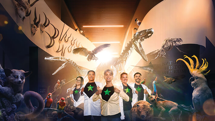 Computer generated composite of research staff holding open their lab coats to reveal a tee shirt with large star, surrounded by exhibits from the NAtural History Museum including dinosaur skeletons and native animals