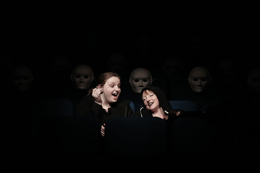 Two laughing girls are unaware of the presence of three figures in plain white masks emerging from the darkness behind them
