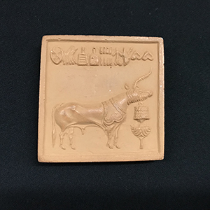 Square terracotta stamp with agricultural scene
