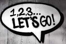 Grey-scale graffiti of speech bubble on fence with words '1,2,3, let's go!'