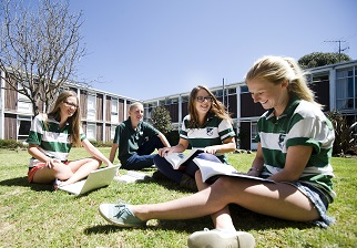 Students discussing their academic work on a lawn outside Robb College.