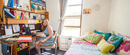 Female student sititng at a desk in a Drummond and Smith college room, and bright cushions on the bed.