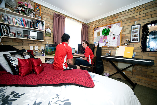 Couple sitting in bedrrom in Wright Village unit, with brick walls, bed, desk and keyboard visible