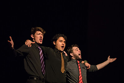 Three male students singing and raising their arms exuberantly