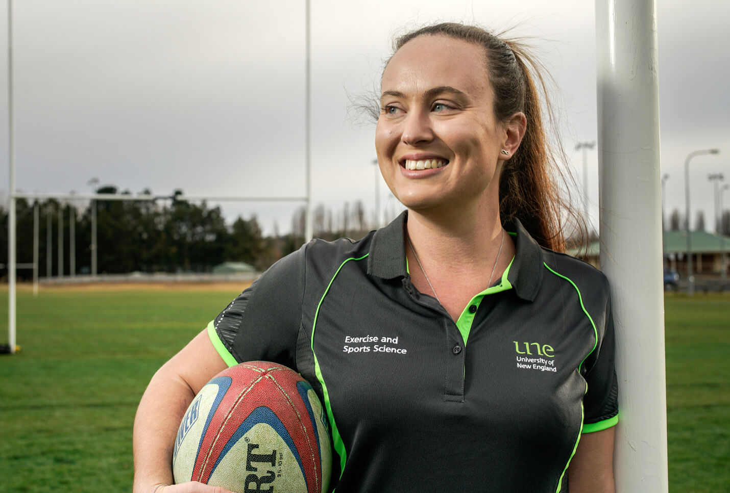 Dr Cloe Cummins standing on a football field, holding a football while wearing her UNE Exercise and Sports Science uniform