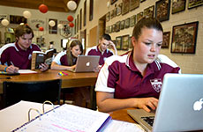 Group of students studying with laptops in Austin College dining hall