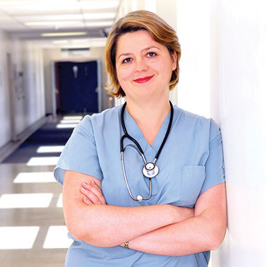 Female nurse dressed in scrubs leaning against the wall