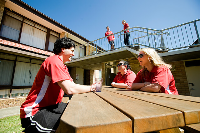 Three students sitting around outdoor table outside two-storey brick unit with two students standing on elevated walkway behind them