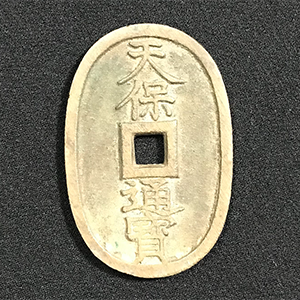 Ancient oval coin with central square cutout and Japanese characters