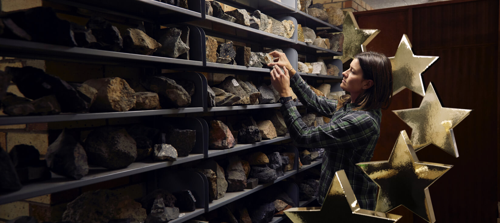 Dr Marissa Betts examining a fossil from a display of specimens with 5 stars in the background.