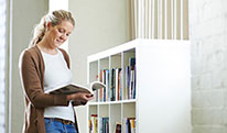 Young woman standing next to a bookshelf with open book