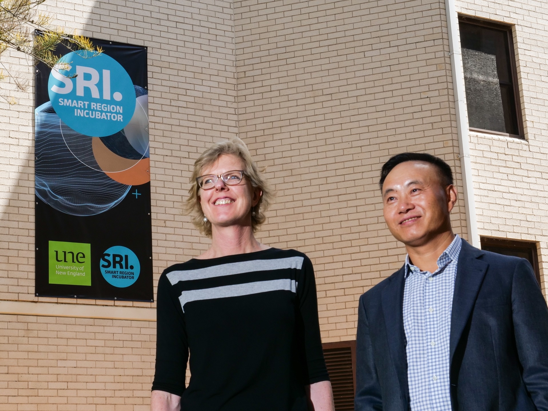 Lou Conway with Dr Zhengrong Shi outside the SMART Region Incubator at UNE