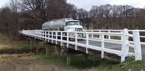 Older multi-span timber bridge with truck crossing