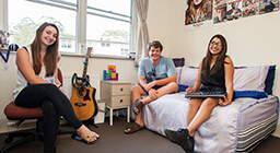 Three students sitting in a Mary White College room with posters on the wall
