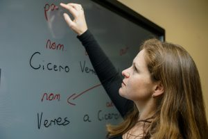 Sarah Lawrence writing latin words on a digital whiteboard with her finger